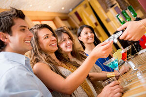Group of people paying for drinks at the bar and smiling